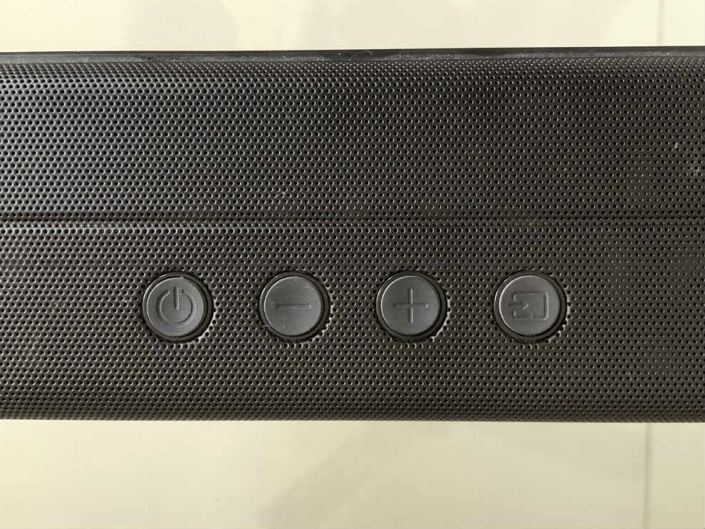 The soundbar has physical buttons on top.